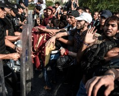 Migrants and refugees try to push a police barricade after they were blocked by Turkish riot police while walking towards Edirne on September 21, 2015 in Istanbul. A new march by migrants trying to reach Europe overland from Turkey was blocked by police outside Istanbul today. Around 700 mostly Syrian men, women and children from a group that had been blocked for the past week at Istanbul's main bus station set out overnight on footfor the northwestern city of Edirne, 250 kilometres (150 miles) away.  AFP PHOTO / OZAN KOSE