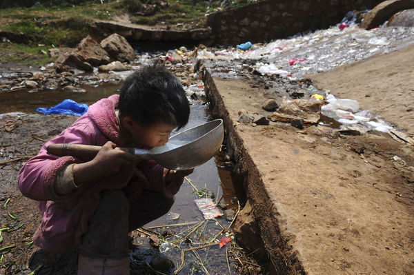 Child drinks from polluted river in Fuyuan County, Yunnan Province.