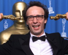 """Actor Roberto Benigni plays with his two Oscars for the photographers backstage at the 71st annual Academy Awards at the Dorothy Chandler Pavilion in Los Angeles, March 21. Benigni won the Academy Award for Best Actor for his role in the film """"Life is Beautiful"""" and he won the Academy Award for Best Foreign Language Film as director. **DIGITAL IMAGE**"""