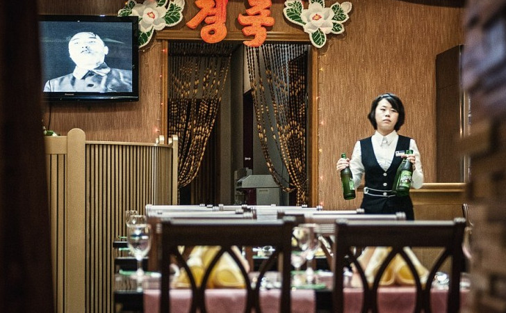 This waitress has to listen to the propaganda all day long while she works. The customers don't get to escape from it either. Photographer Michael Huniewicz put his freedom on the line to get these photos from inside the North Korean world.