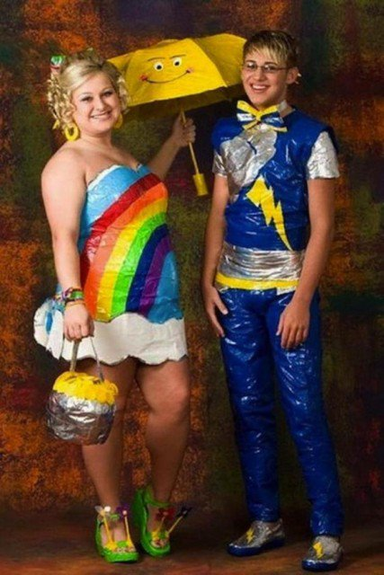 Prom outfits are notorious for stepping with confidence outside established norms. However, it is clear that this couple here has no problem in being the target of everyone's ridicule.  With that rainbow covering your body you might expect people to forget the fact that you are fat and ugly. Add a yellow umbrella just in case a sudden indoor rain starts, and you have the perfect outfit. Oh, we forgot about the boy.